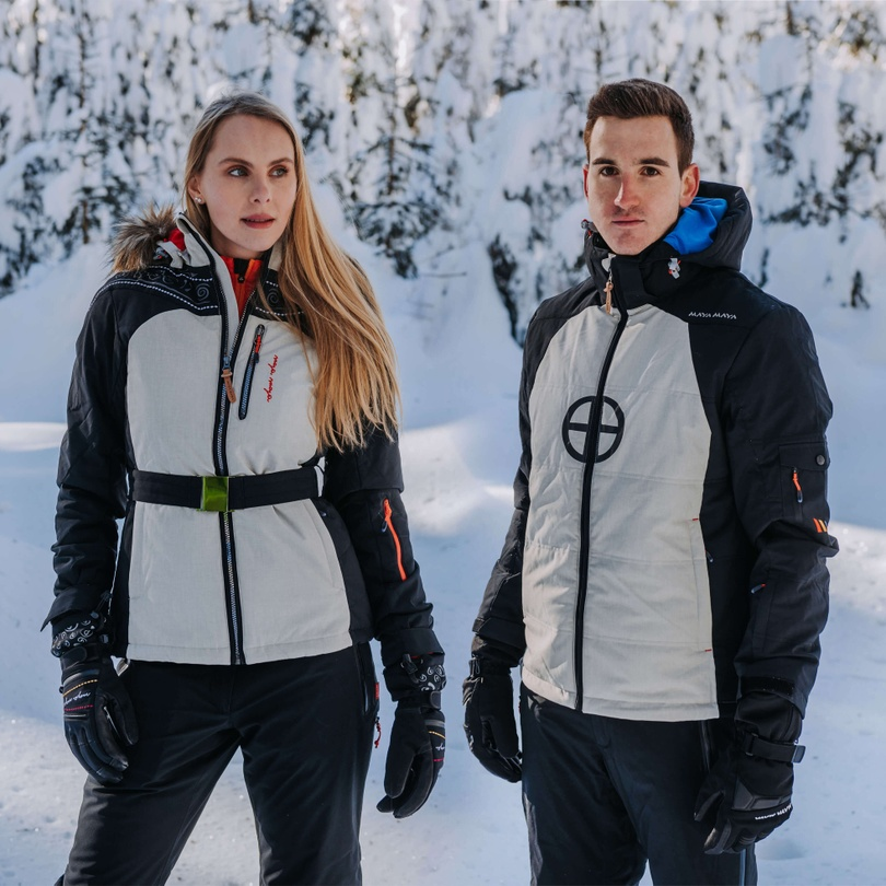 Man and lady wearing ski jackets and pants by MAYA MAYA